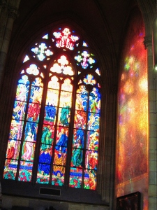 I was stunned by the view of morning sunlight streaming through this stained glass window in St. Vitus, overlaying the wall next to it with vivid colours.