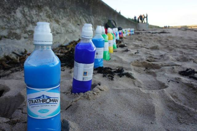Our mothers lined up a huge row of paint bottles along the beach!